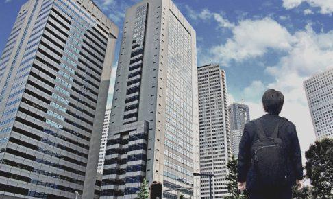ビルディングを見上げながら野望を抱くビジネスマンのイメージ画像