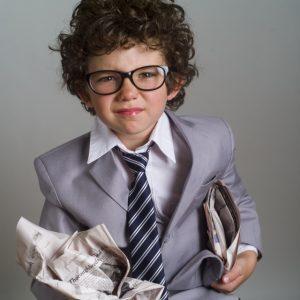 新聞をクシャクシャにして顔をしかめる子どものイメージ画像